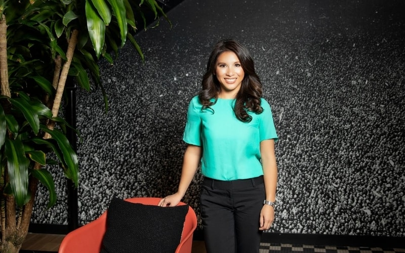 Woman in teal blue shirt standing by red chair with black background.