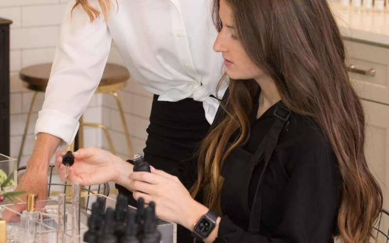 Woman creating her own fragrances with help from professional.