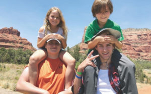 Two older brothers holding their younger siblings (brother and sister) on their shoulders for photo at Grand Canyon.