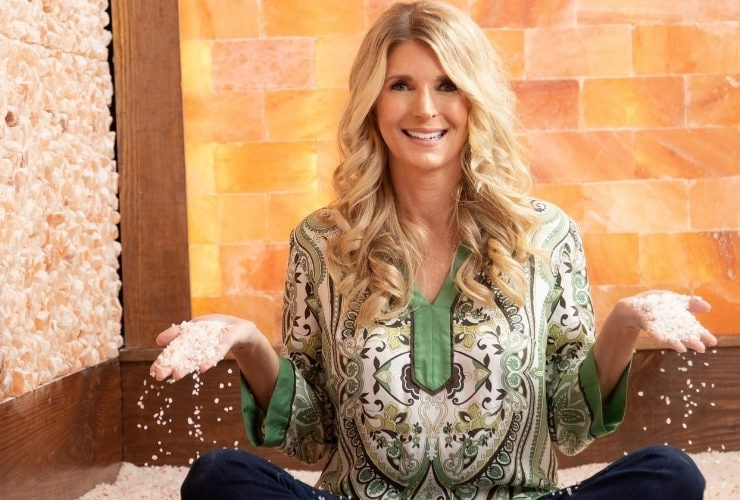 Woman in Salt Therapy studio sitting criss-cross holding salt in both hands.