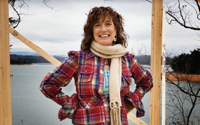 Woman wearing red flannel standing on a construction site at the lake.