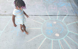 Little girl looking at sunshine chalk drawing on her driveway.