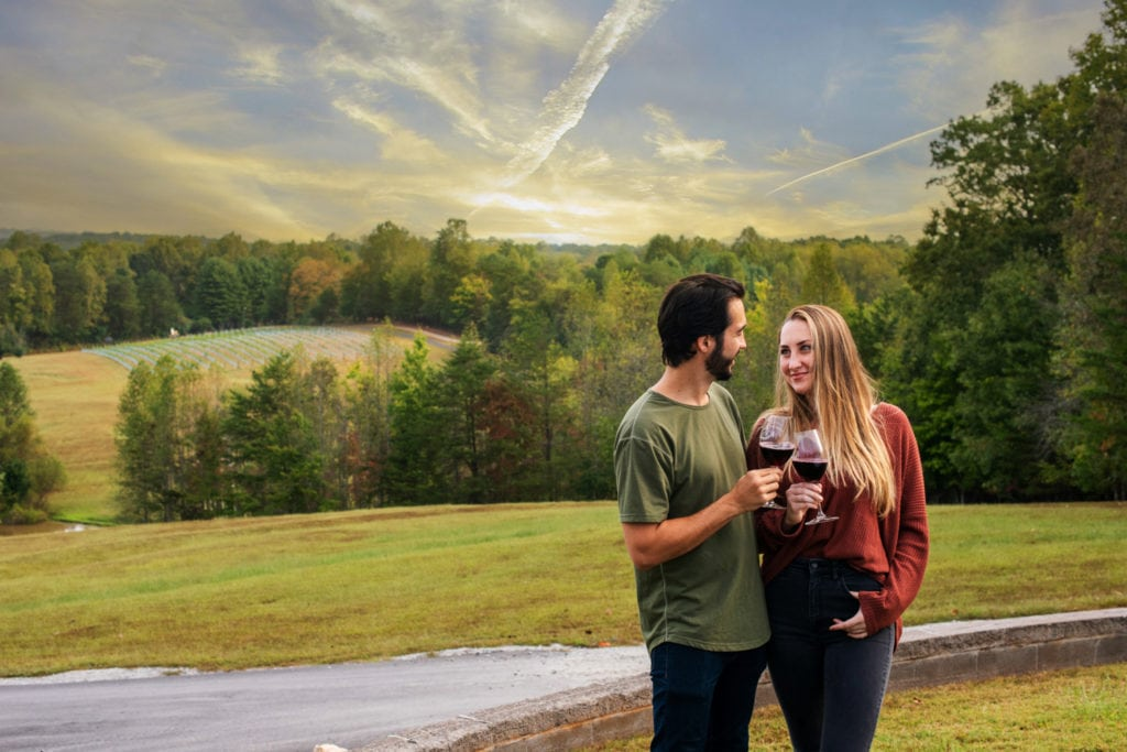 Young couple with wine glasses in the countryside