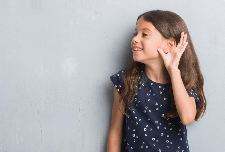 Little girl in blue shirt in front of gray wall with hand up to ear