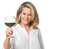 Kristen Coffield with glass of green juice in wine glass