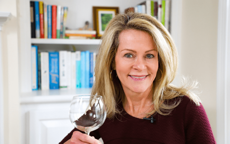 Kristen Coffield in front of bookshelf with wine glass